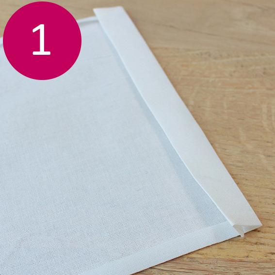 Etape 1 : Découpez 2 rectangles de coton de 20 x 26 cm. Faites un petit repli de 5mm sur les 2 cotés du coton. Réalisez un ourlet sur la partie haute : pliez à 1 cm le coton, repassez puis repliez sur 1,5 cm. Repassez pour maintenir le tissu. Réalisez la même chose sur le second coupon.