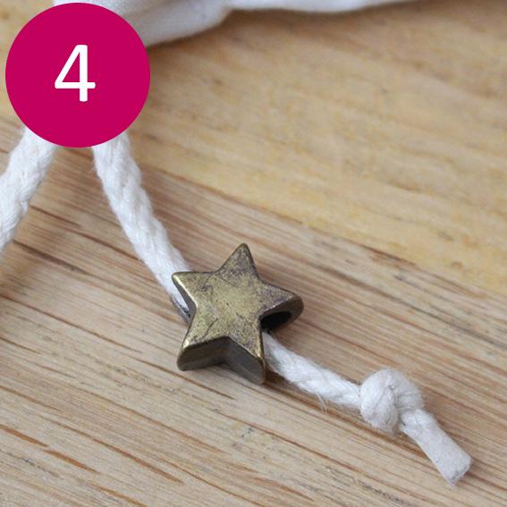 Etape 4 : Coupez le cordon en 2 petits cordons de 30cm. Passez les cordons dans chacun des passants. Positionnez l'embout cordon, réalisez un nœud en bout et coupez le surplus si besoin.